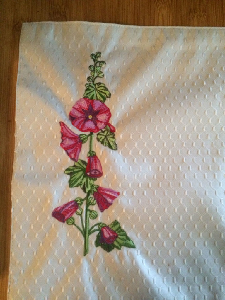 maroon red holly hocks on beige table mat